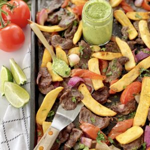 beef and fries and green sauce on a baking sheet