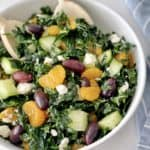 kale salad in a bowl with oranges and a spoon