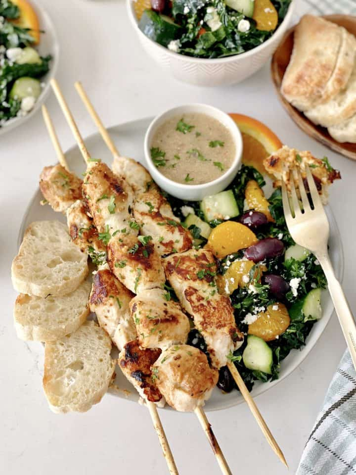 plate with skewers and kale salad with fork