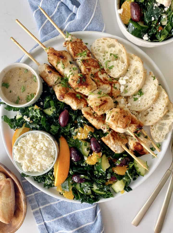 close up of chicken skewers, kale salad, bread slices