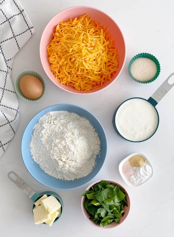 bowl of flour cheese, egg milk and chopped spinach