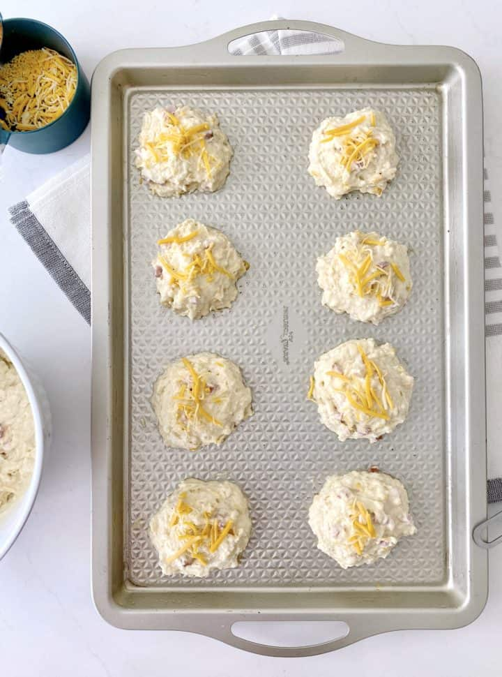 dropped biscuits on a baking sheet with cheese on top