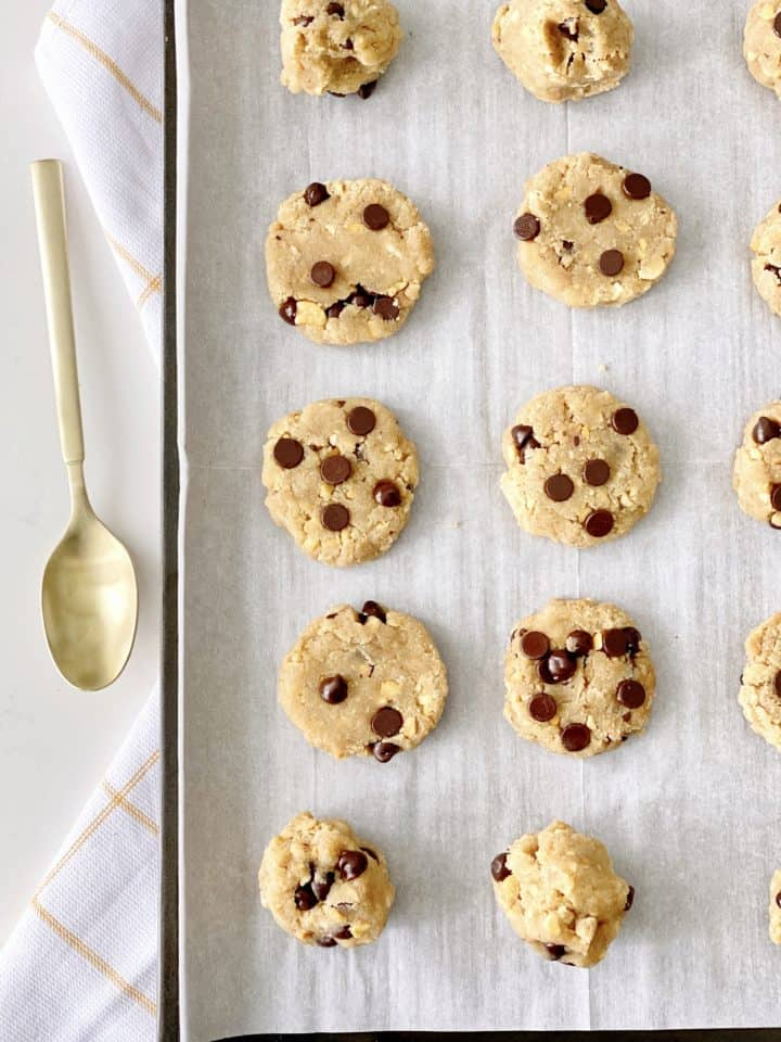 flattened chocolate chip cookies on a parchment lined baking sheet