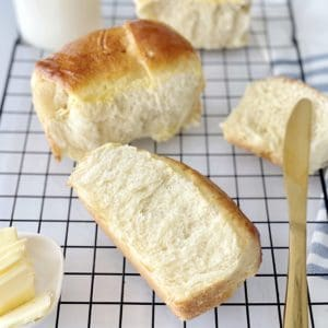 baked bread rolls on a wire rack with butter knife