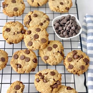 cookies on a wire rack with chocolate chips in a bowl
