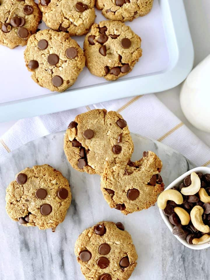 cookies on a plate with cashews and chocolate chips on the side