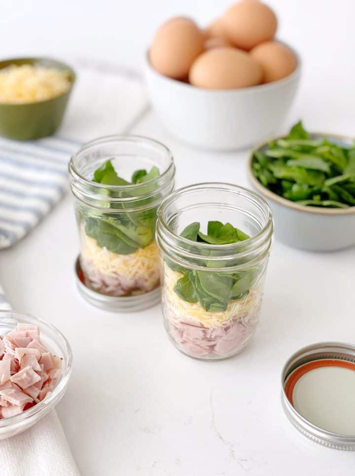 mason jars with fillings like spinach cheese and ham to make microwave scrambled eggs