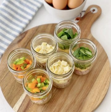 mason jars of toppings for egg scramble on a wood board
