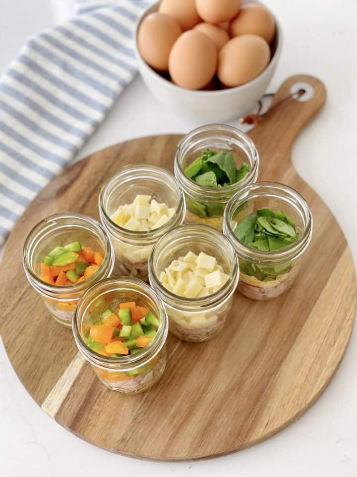 mason jars of toppings for scrambled eggs on a wood board