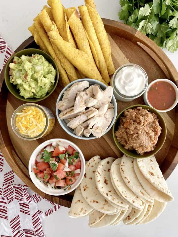 board of chicken, salsa, guacamole, taquitos, sour cream and tortillas