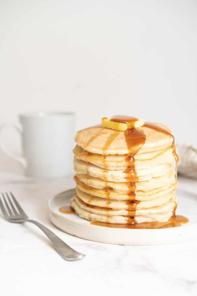 Stack of pancakes with maple syrup and butter on top on a plate