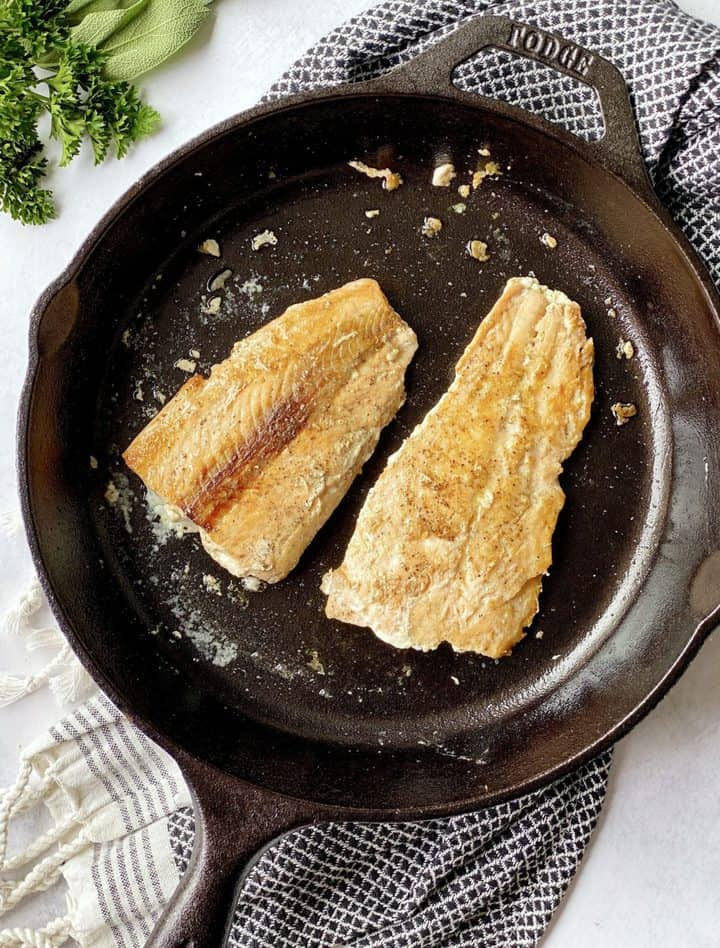 cooked salmon on a skillet with oil