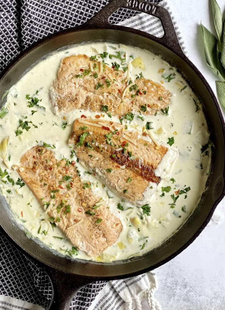 pan with cream sauce and salmon filets in a pan