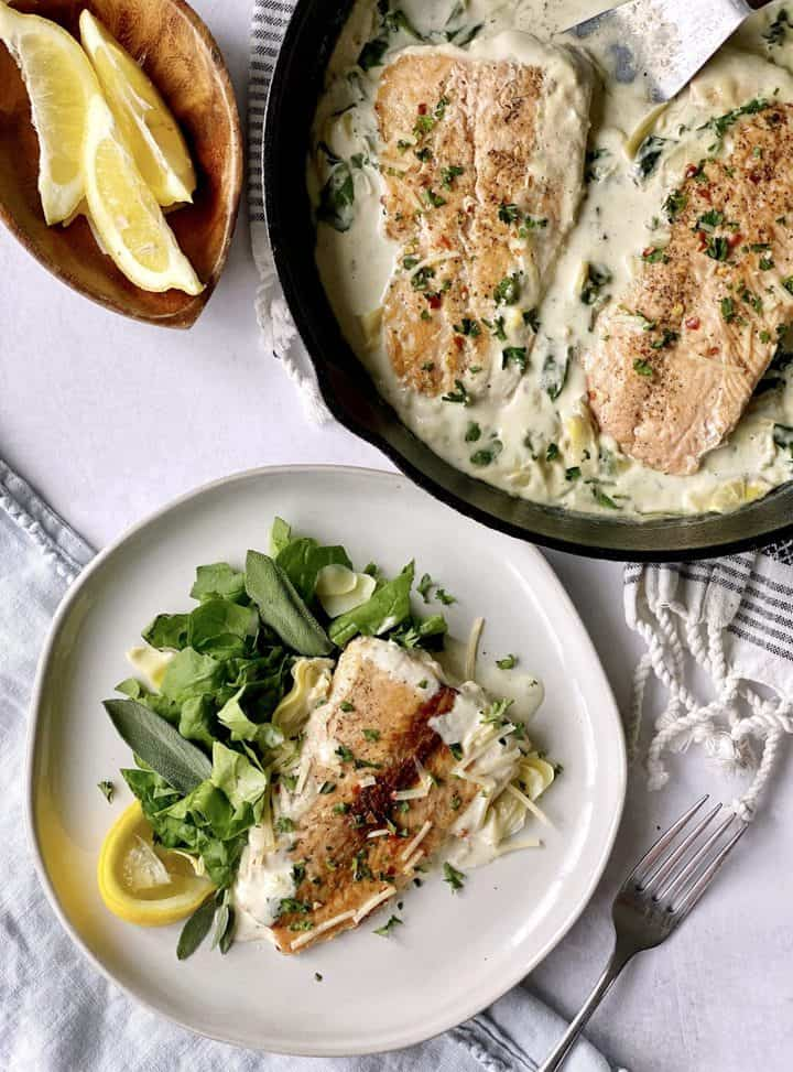 serving portion of creamy pan fried salmon with pan of salmon