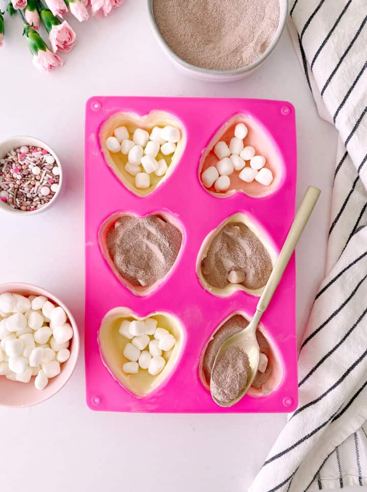 heart molds filled with chocolate, marshmallows, hot chocolate mix