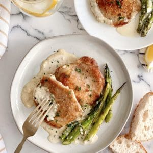 plate of pork chop with asparagus and cream sauce