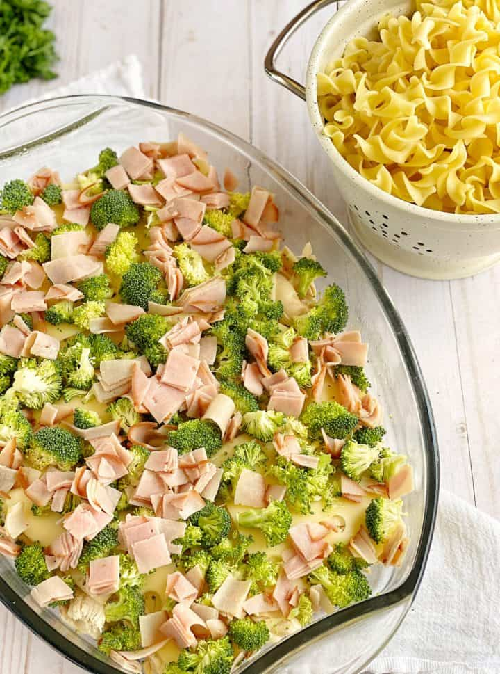 baking dish with layered ingredients including broccoli and noodles
