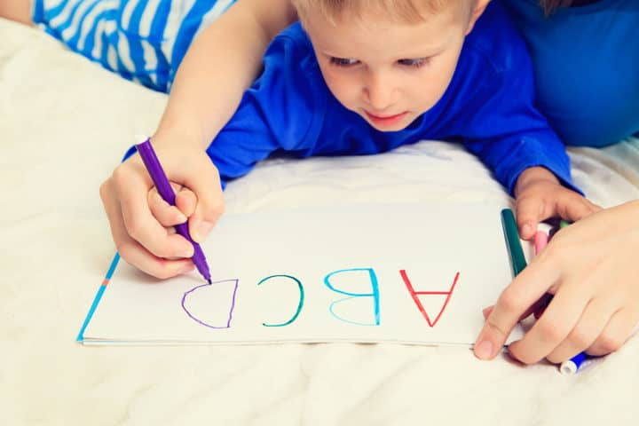 boy tracing letters with parent