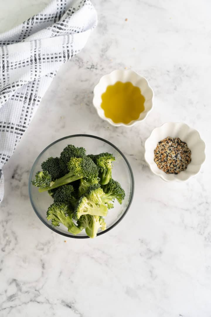 broccoli in a bowl with olive oil in a bowl and seasonings in a bowl