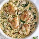pan with orzo and spinach and chicken thighs in a pan