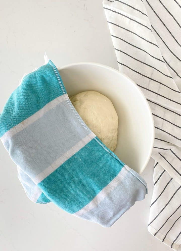 bowl with dough inside and a towel over it