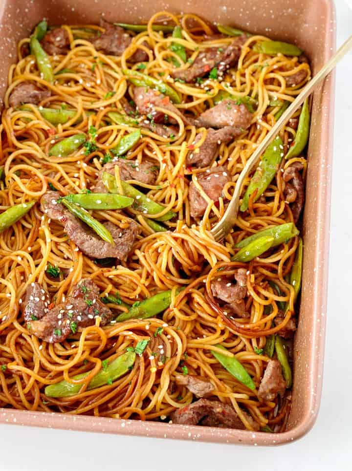 close up of noodles in a dish with snow peas and beef