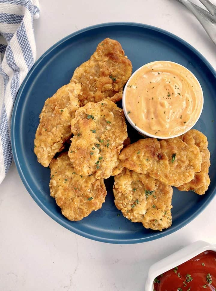 vegan chicken nuggets on a blue plate with dip