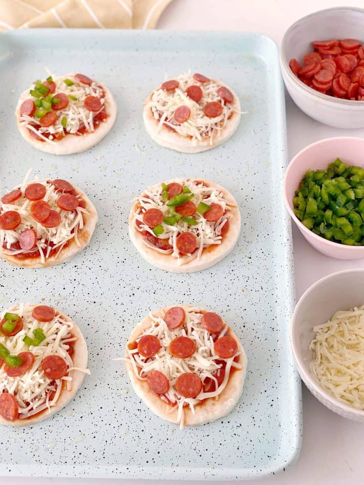 raw pizza dough with green peppers, pepperoni and cheese next to some ingredients bowls