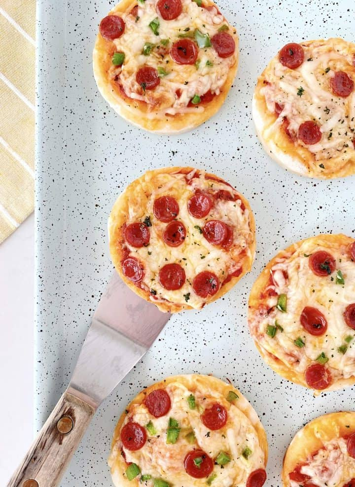 mini pizzas with a spatula on a baking dish