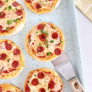 close up of mini pizzas in a baking dish