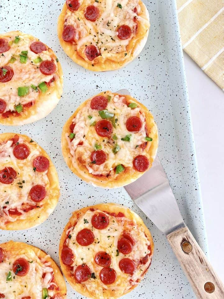 mini cauliflower pizzas on a bakign sheet with a spatula