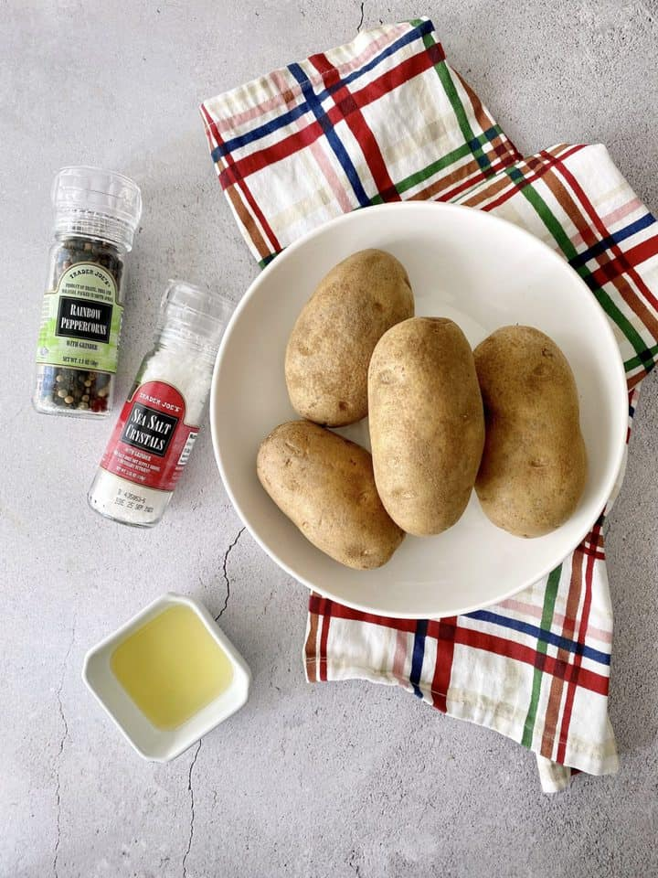 ingredients for baked potato in air fryer, potatoes, pepper, salt, and olive oil