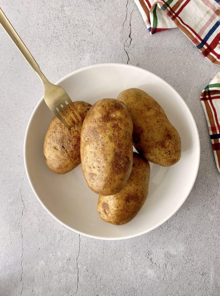 fork in potatoes with other potatoes in a bowl