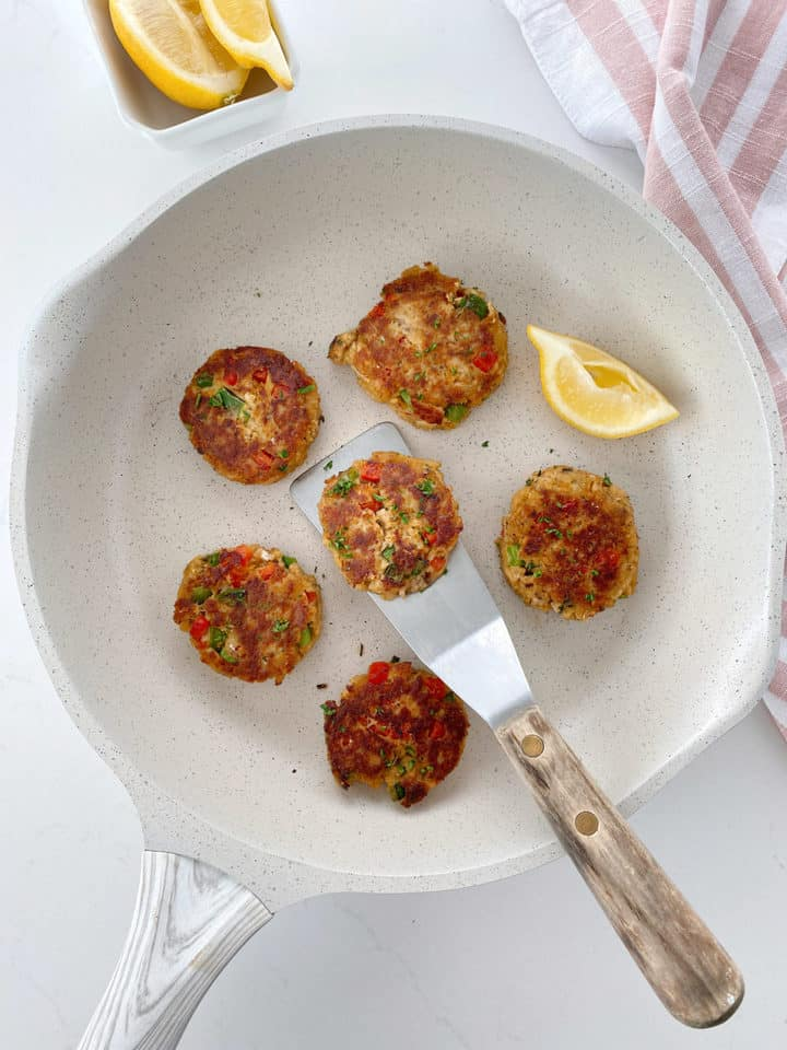 pan with salmon patties on it and a spatula