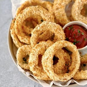 bowl of onion rings next to ketchup