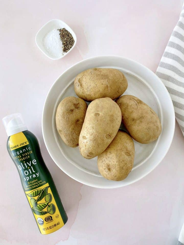 bowl of potatoes next to olive spray and seasonings