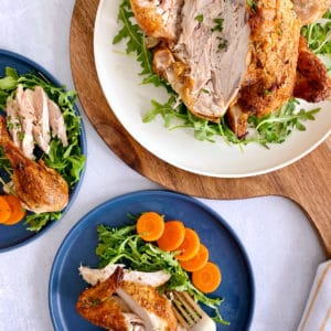 whole chicken next to plated servings of chicken and vegetables