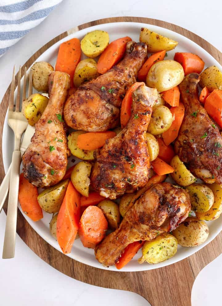 plate of chicken legs with potatoes and carrots