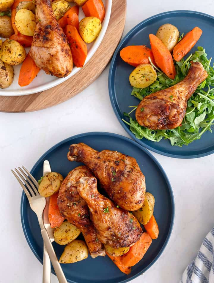 air fryer chicken legs with served plates of potatoes and carrots