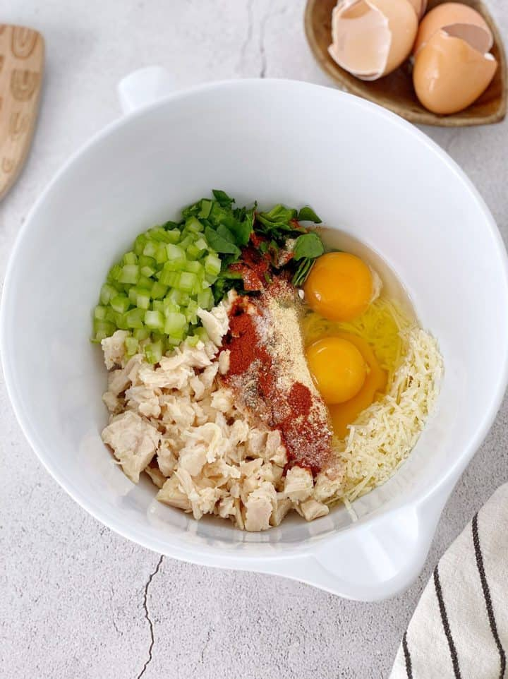 bowl of ingredients including chicken, spinach, eggs, parmesan cheese and seasonings