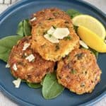 chicken patties on a blue plate with slice of lemon