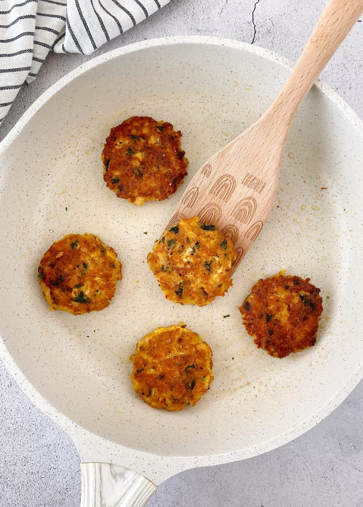chicken patties on a pan with wooden spoon
