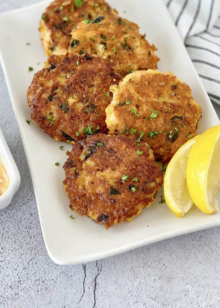 close up of chicken patties with lemon slices on the side
