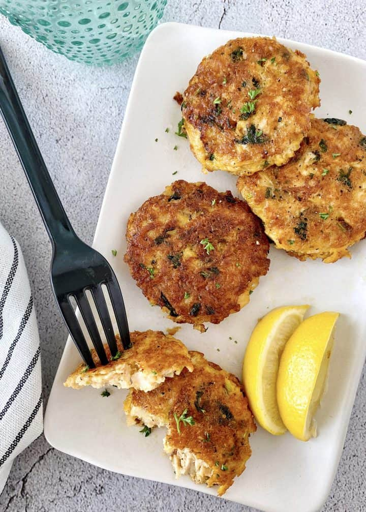over the top shot of chicken patties with lemon slices and fork