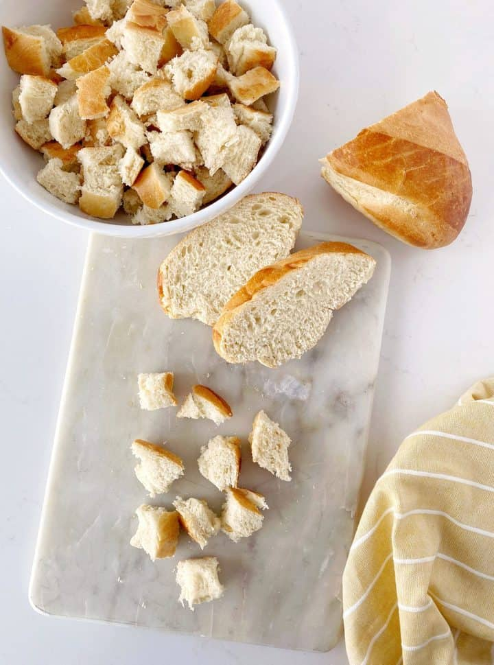 board with cut up bread and a bowl of cut bread