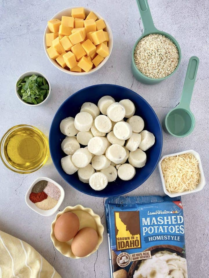 over the top shot of ingredients including bag of pototoes, cheese, breadcrumbs and seasonings, and eggs