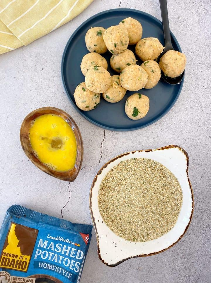 bowl of eggs and breadcrumbs with formed potato balls on a blue plate