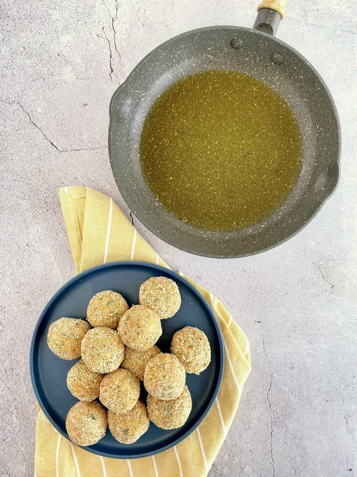 potato balls on a blue plate and a pan with oil