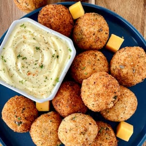 mashed potato balls on a blue plate with a dip