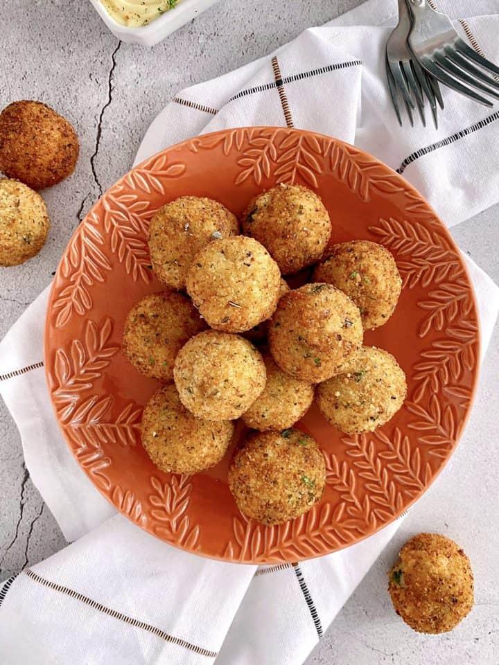cooked potato balls on an orange plate